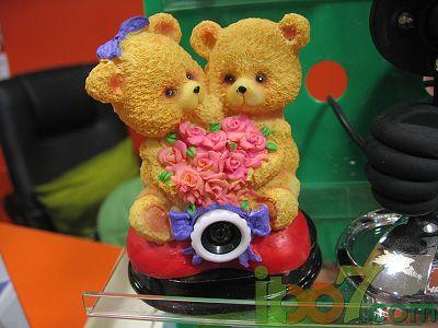一对可爱的小熊抱着一束心形的红玫瑰坐在大红色的地毯上,看上去关系