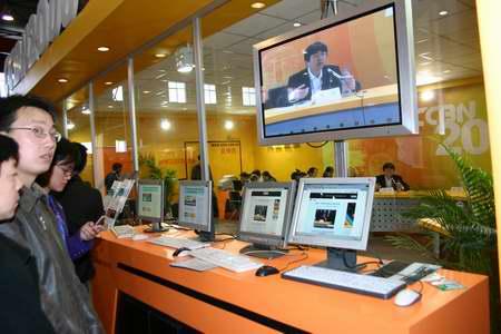 科技时代_图文:现场观众通过网络查看高峰论坛视频直播