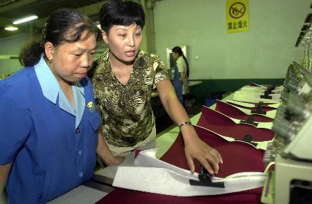市场部副总经理指导一名工人生产