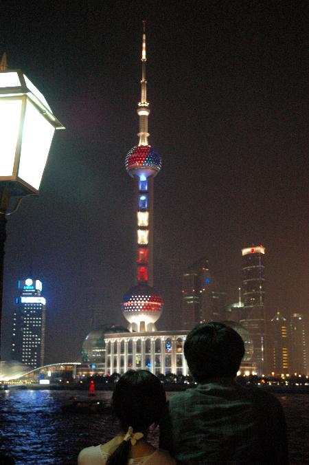 10月10日晚,上海东方明珠电视塔景观灯光呈现出象征法国国旗颜色的