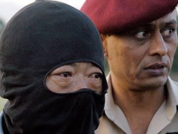 图文:戴着面罩的王恩德由巴基斯坦士兵的护送