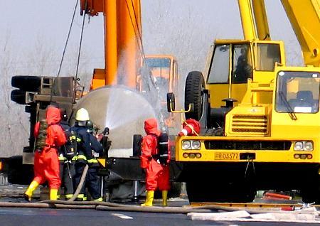 图文:消防队员在泄漏事故现场进行清理工作