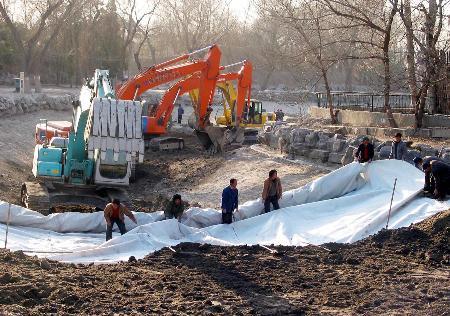 图文:工人们正在圆明园湖底铺设防渗膜