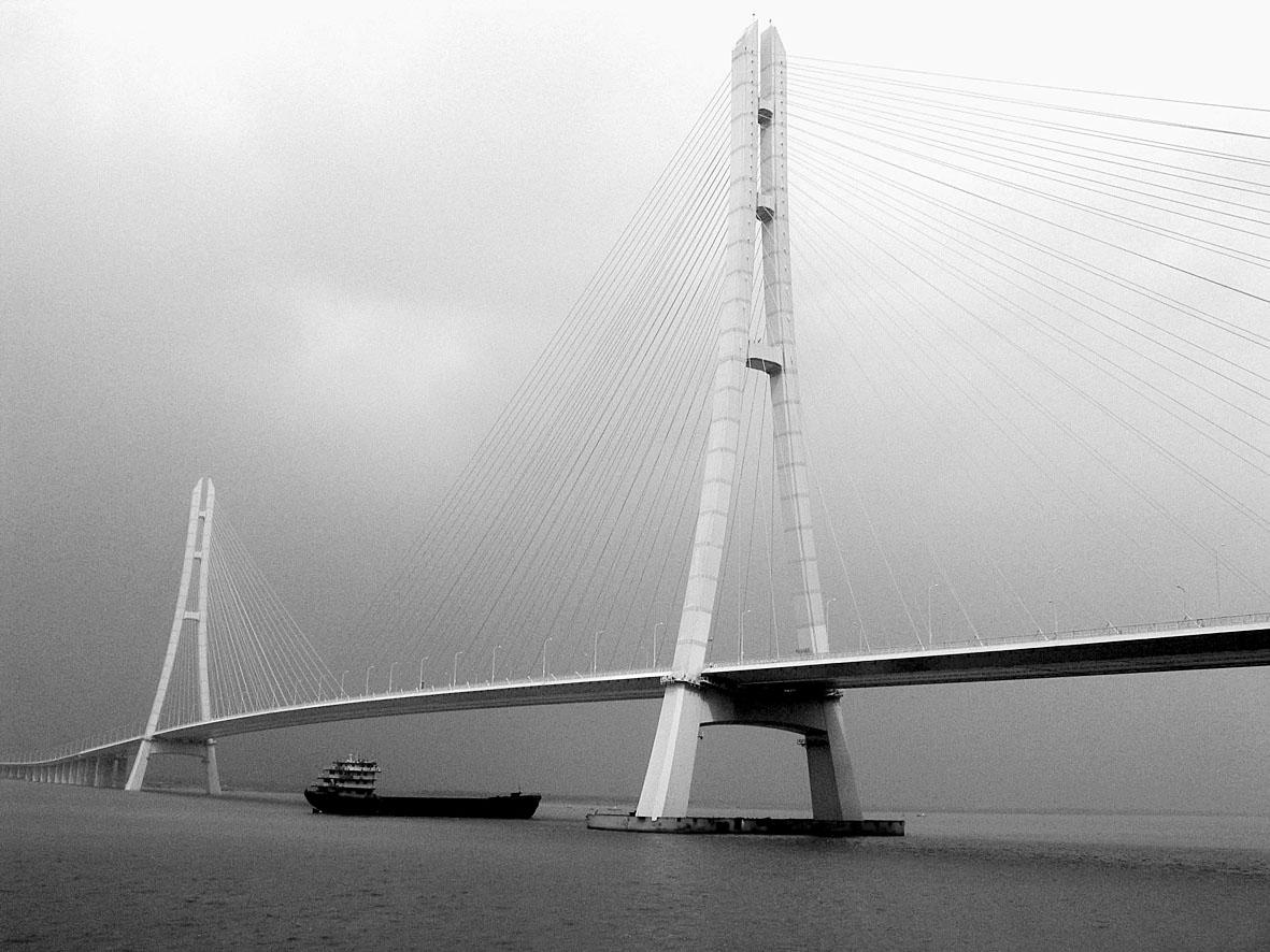 """首次采用高215米,""""人""""字弧线形全钢结构索塔."""