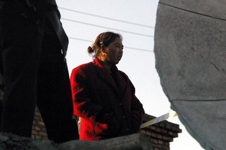 刘宏鹏/10月28日,在乌苏市中兴煤矿,一名矿工家属在警戒线外等候消息...