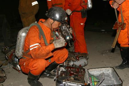 乌苏市/一名准备下井抢险的矿山救护队员在检查瓦斯监测器
