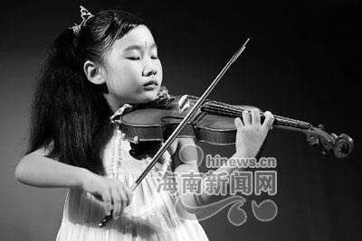 的伍钉钉在表演小提琴独奏《庆丰收》.-第三届金椰奖颁奖