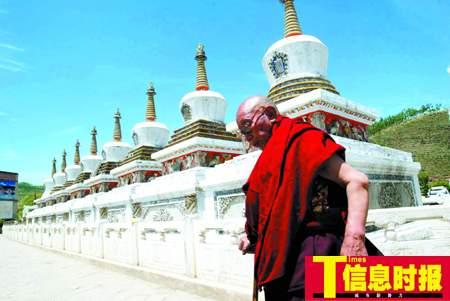 一名喇嘛正围着塔尔寺的八座白塔念经