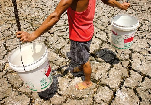 图文:村民挑着空水桶从开裂的池塘走过