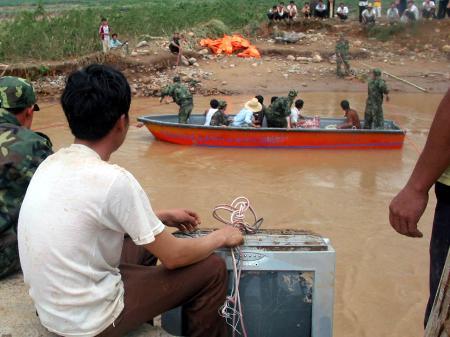 图文:村民守着泥迹斑斑的电视机等待救援