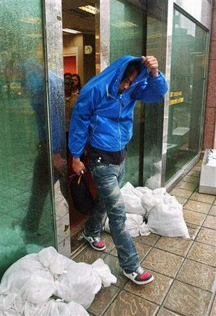 图文:男子用衣服遮风雨
