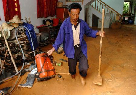 图文:一位村民从满地泥浆的房间里搬运农具