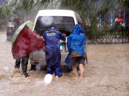 图文:3名党员在推移被洪水围困的车辆