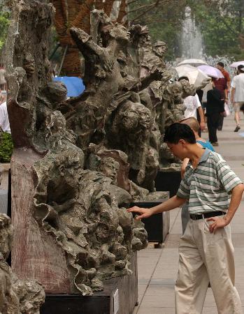 """图文:重庆:不文明行为使抗战雕塑""""受伤""""(2)"""