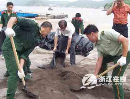 图文:台门边防派出所指战员正在加固堤防