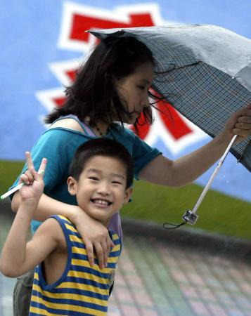 图文:上海街头一名儿童打出象征胜利的手势