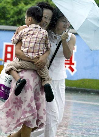 图文:一名儿童依偎在家长怀里冒着风雨赶路