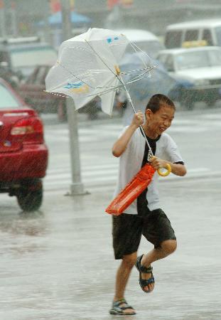 图文:大连街头一男孩在雨中前行