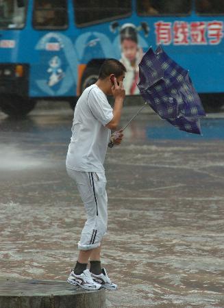 图文:行人雨伞被风吹翻转