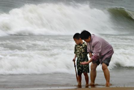 图文:两名游客在河北秦皇岛海滩上玩耍