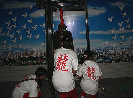 图文:参观展览的中学生抚摸和平大钟