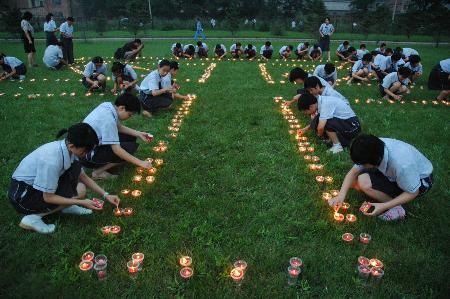 图文:哈尔滨市孩子们用点燃的蜡烛组成和平二字