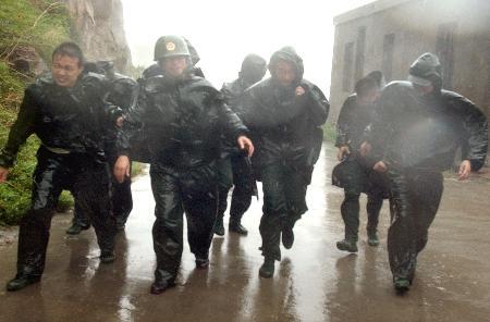 图文:工作人员冒着狂风暴雨在海港大堤上巡查