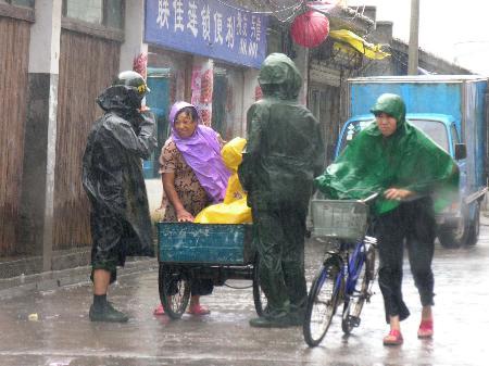 图文:边防官兵在风雨中劝说村民赶紧回家躲避