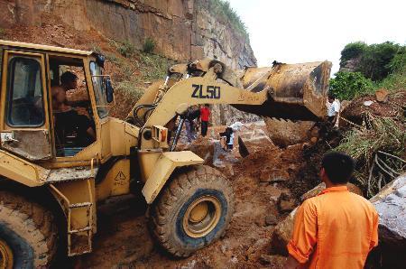 图文:福建施工人员在清理堵塞在国道上的土石