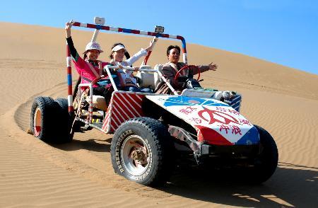 图文:游客乘坐沙漠越野车冲下一座沙丘