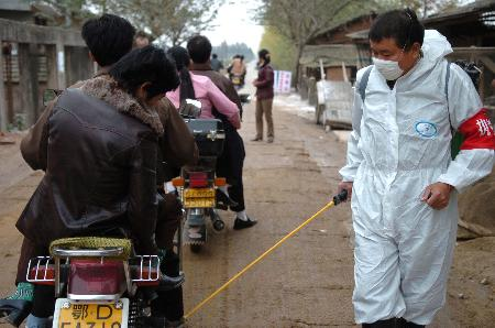 图文:湖北石首防疫人员为过往车辆消毒