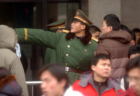 图文:战士在向旅客指点车站售票处的位置