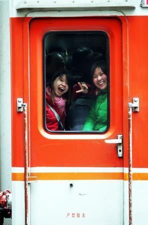 图文:女孩儿在拥挤的火车过道内向窗外挥手