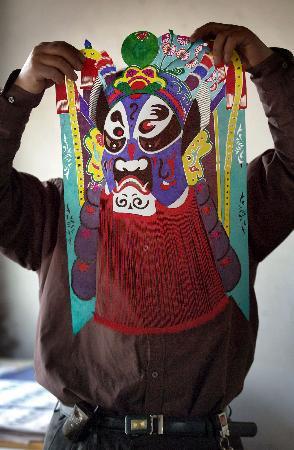图文:剪纸艺人在展示自己的京剧脸谱作品