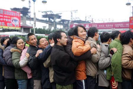 图文:农民工在重庆火车站临时列车购票处排队