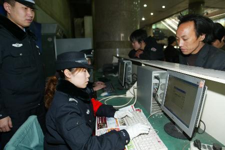 图文:警察在候车大厅进行网上追逃人员比对