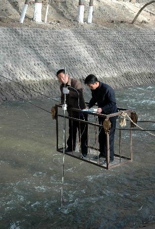 图文:水文局工作人员正在测量河水流速
