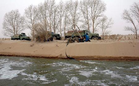 图文:民勤植树造林的工作人员在水渠取水