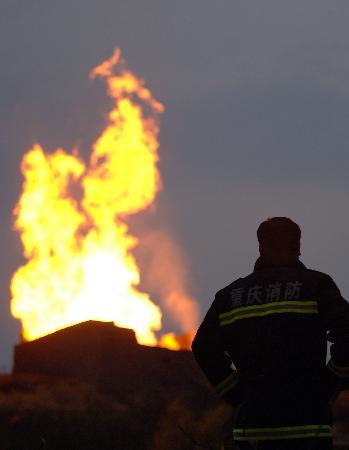 图文:消防战士在事故现场小土丘上观测