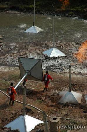 图文:工人在河床上搬运引燃漏气的锥形器