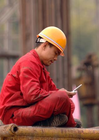 图文:石油工人坐在井架前给家人发短信报平安
