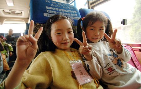 图文:两名小女孩高兴地坐上返乡客车