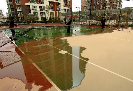 图文:北京小区冲洗网球场沙尘