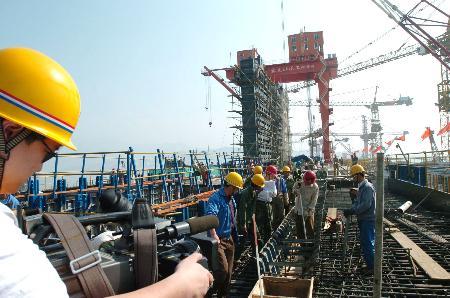 图文:记者在拍摄青云水利水电联营公司职工备仓情况