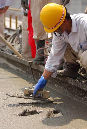 图文:施工人员在进行平仓前的最后一抹