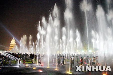 客和市民在西安大雁塔广场上的音乐喷泉纳凉.-西安音乐喷泉吸引市