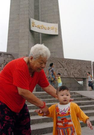 图文:老人带着孩子在唐山抗震纪念碑广场游玩