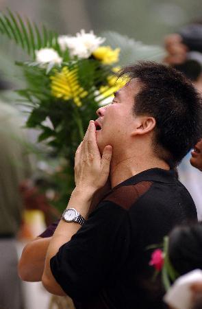 图文:一名悼念者在唐山地震纪念墙前哭泣
