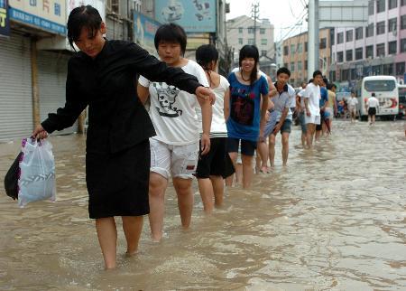 图文:温州苍南县人们正小心通过积水路段