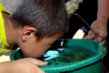 图文:少年在饮用刚打上来的井水